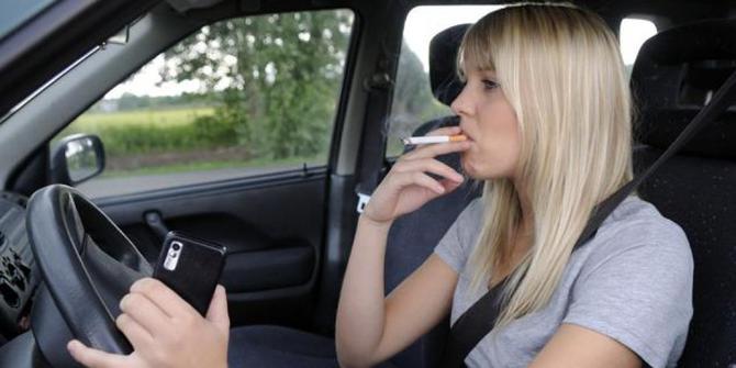 Wanita memakai baju ungu sedang memegang ponsel dan merokok dalam mobil