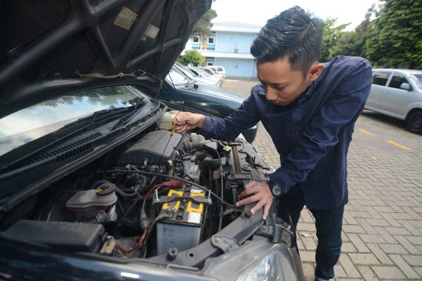Pria ini sedang melakukan periksa kondisi mesin mobil bekas