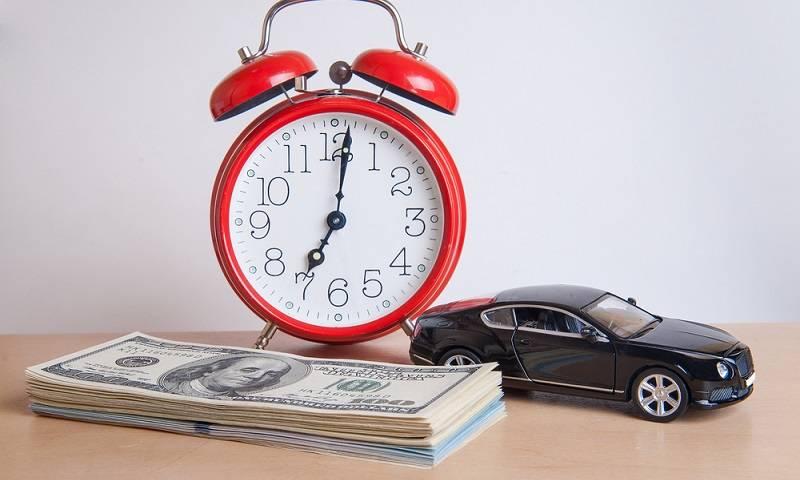 Jam diding berwarna merah, uang dolar dan mobil