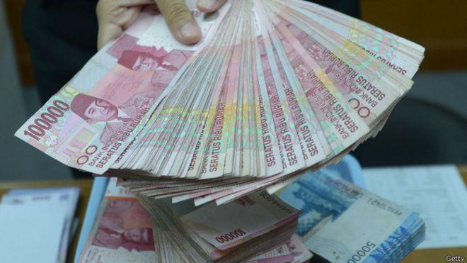 puluhan kertas uang seratus ribu rupiah