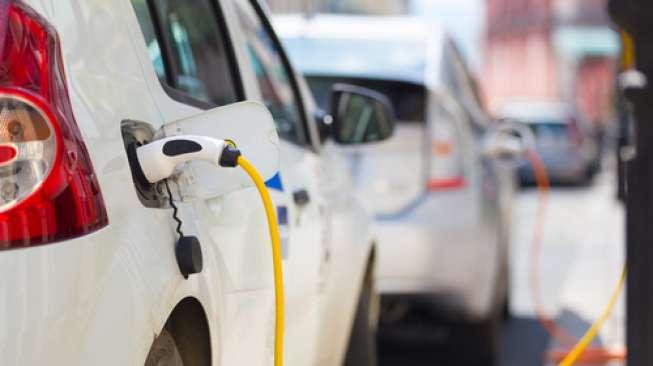 sebuah mobil sedang mengisi baterai di tempat pengisian listrik