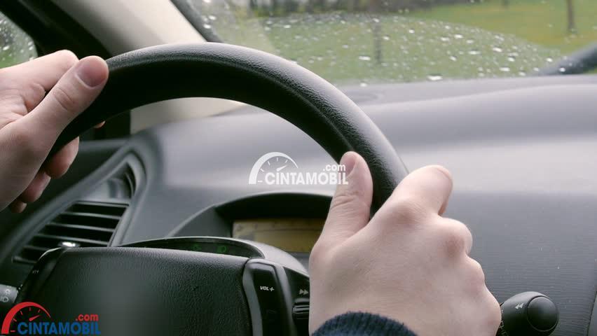 Seorang pria memegang setir untuk mengendalikan mobil dalam hujan