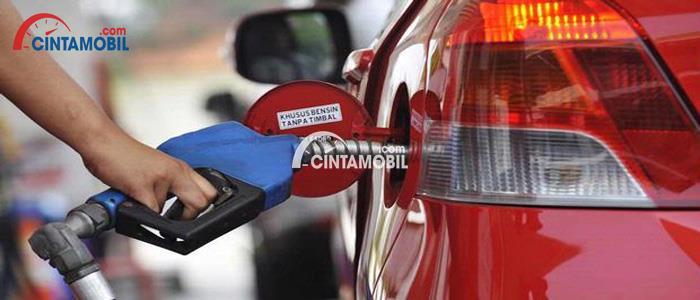 Tangki bensin mobil dibuka dan seorang karyawan mengisinya