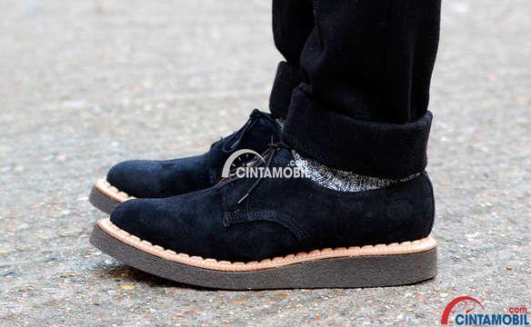seorang memakai sepatu bersol tebal berwarna hitam sedang duduk di jalan