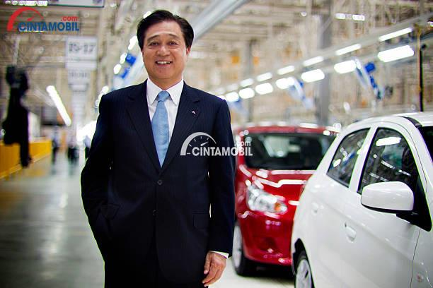 CEO Mitsubishi, Osamu Masuko sedang tersenyum di sampingnya ada dua mobil putih dan merah
