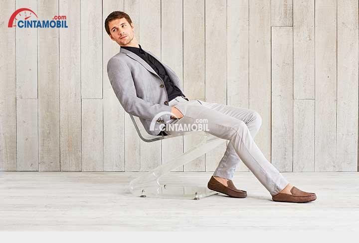seorang kantoran sedang duduk di kursi dalam sebuah kantor sangat sepi
