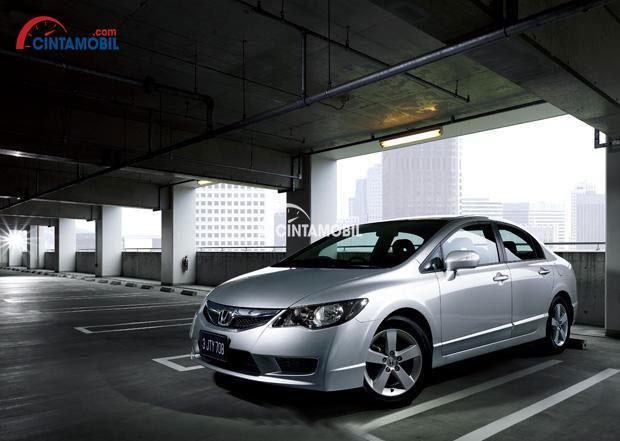 Gambar mobil Honda Civic 2008 berwarna silver dilihat dari bagian depan sedang parkir di dalam gara mobil