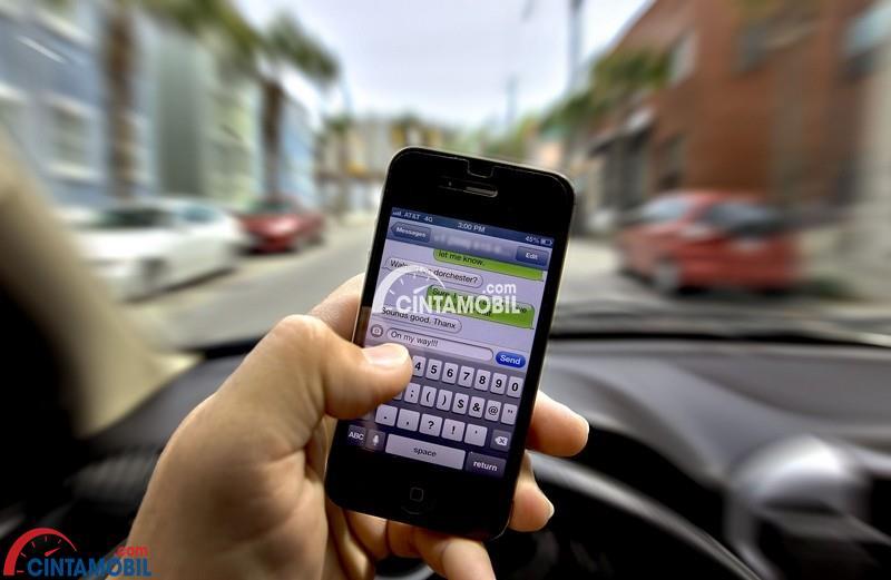 seorang sedang menggunakan ponsel untuk menulis SMS sambil mengendarai mobilnya