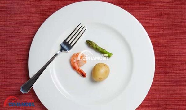 gambar yang menujukan piring dengan udang, asparagus dan kentang serta sebuah garpu