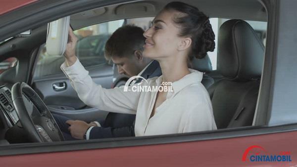 Seorang pria yang sedang duduk di samping wanita yang sedang menyetir