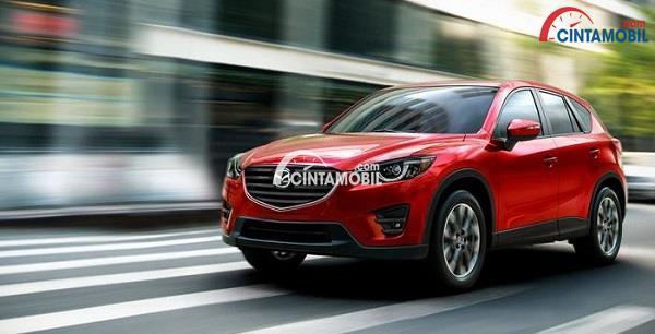 mobil Mazda CX-5 berwarna merah bergaya sporty yang sedang melaju kencang di jalanan kota