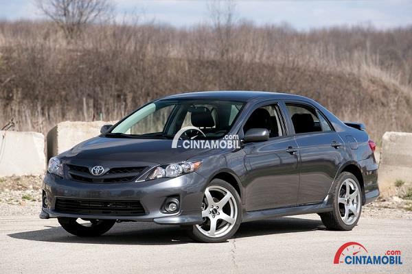 Toyota Corolla tahun pembuatan 2013 berwarna hitam dengan latar belakang hutan