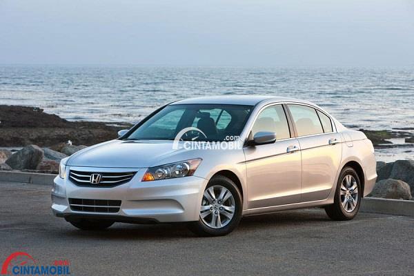 Honda Accord tahun produksi 2012 berwarna putih dengan latar belakang laut dan deburan ombak