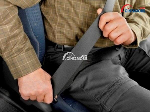 Gambar penumpang yang sedang mengikatkan sabuk pengaman secara manual