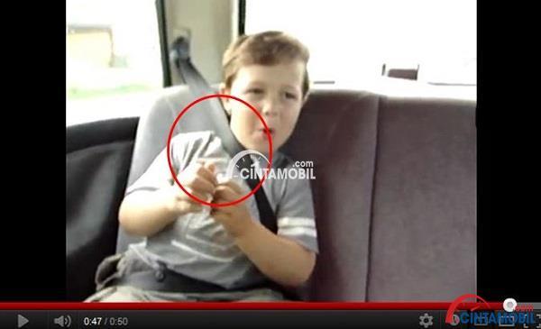 Gambar seorang anak yang memakai sabuk pengaman secara salah ditunjukan dengan lingkaran merah