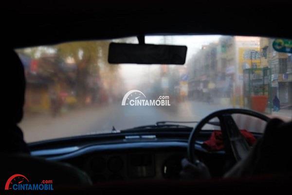 Gambar jendela depan mobil yang berkabut karena hujan turun