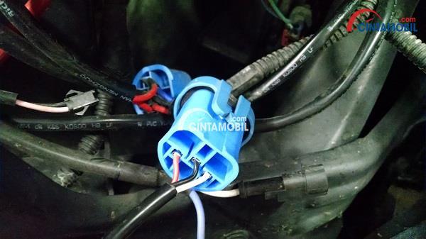 Kabel daya dengan steker berwarna biru yang terpasang pada lampu depan mobil
