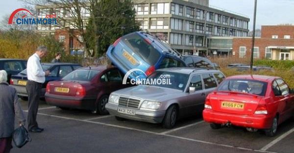 Parkiran yang dipenuhi oleh mobil yang saling menghimpit satu sama lain