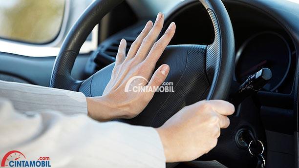 Gambar yang memperlihatkan tangan yang sedang menekan klakson mobil