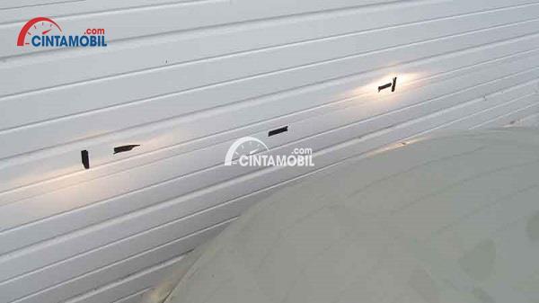 Gambar yang memperlihatkan selotip pada dinding yang disinari dengan lampu depan mobil