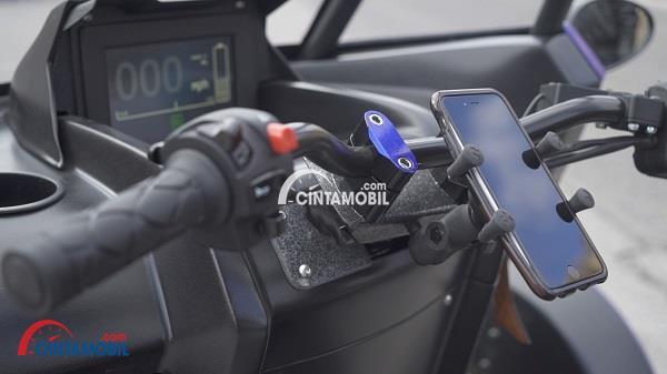 Mobil Arcimoto yang mempunyai setang berwarna hitam dengan smartphone tertancap