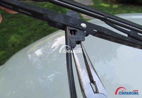 Gambar yang menunjukan pisau wiper dibuka menggunakan tang berhidung jarum untuk menahan bilah wiper