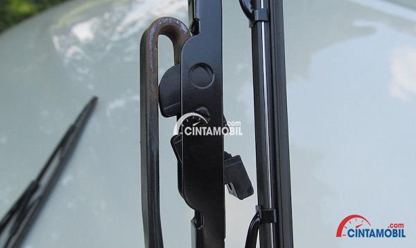 Gambar yang menunjukan bilah wiper baru yang sedang dimasukan pada bagian lengan wiper
