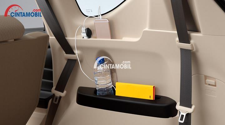 Power Outlet dalam sebuah mobil dan ada botol air dan Iphone berwarna golden dalamnya