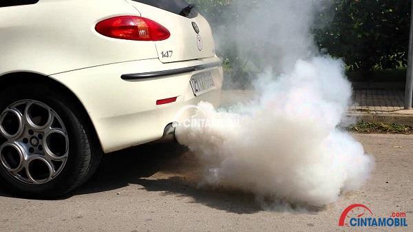 Mobil berwarna putih yang mengeluarkan asap berwanra putih dari knalpotnya
