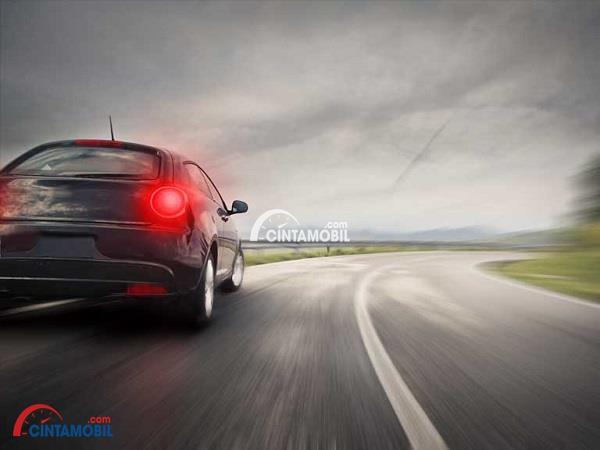 Gambar yang memperlihatkan mobil berwarna hitam yang sedang mengerem ktika melaju kencang