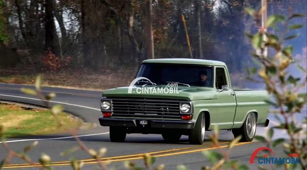 Mobil pick up berwarna hijau yang sedang berkendara di jalanan pada pagi hari