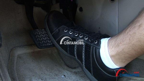 Gambar yang memperlihatkan kaki yang sedang memakai sepatu berwarna hitam yang sedang menekan pedal rem pada mobil