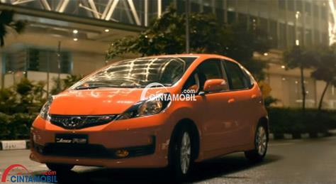 Gambar mobil Honda Jazz 2013 berwarna orange sedang parkir di samping gedung tinggi di Indonesia