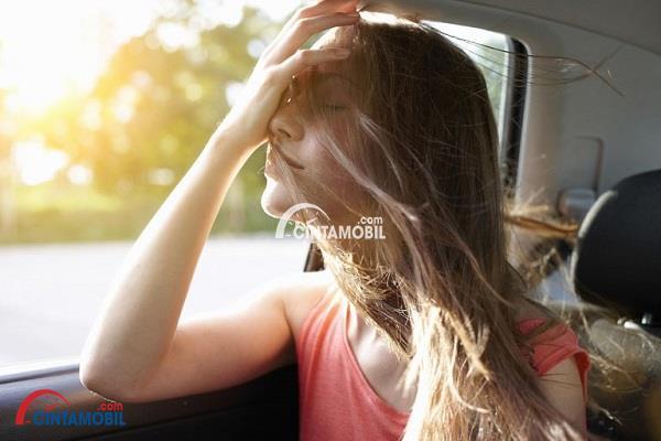 Gambar wanita berbaju pink yang sedang menikmati udara dari dalam mobil