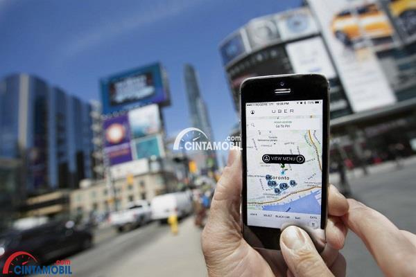 Gambar aplikasi Uber yang dipegang oleh tangan yang diangkat di daerah perkotaan