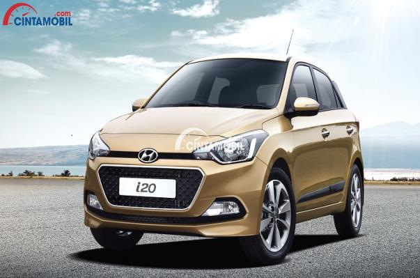 gambar Hyundai i20 berwarna golden dilihat dari bagian depan sedang parkir di depan pantai di Indonesia