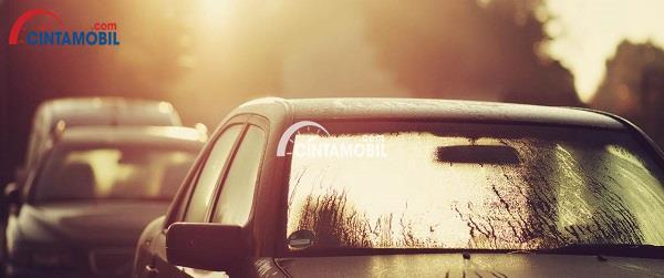 Gambar yang memperlihatkan bagian kaca depan mobil yang sedang disinari mentari di pagi hari