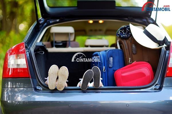 Bagian bagasi mobil dengan dua pasang kaki anak-anak yang sedang bersantai