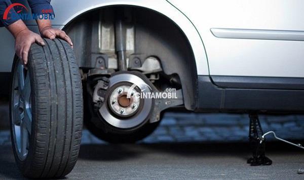Gambar yang menunjukan mekanik yang sedang membuka ban dari mobil berwarna putih