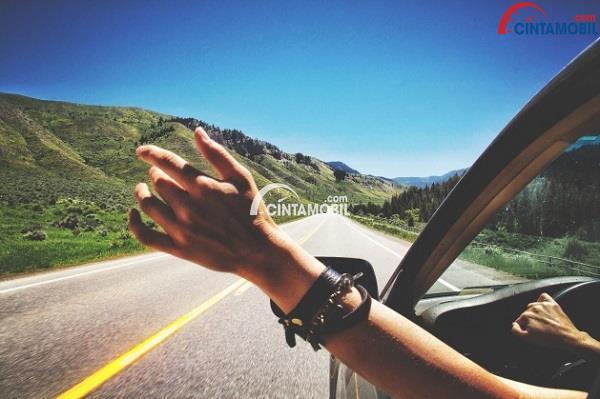 Tangan yang sedang keluar dari jendela mobil yang melaju di jalanan kosong dengan langit biru