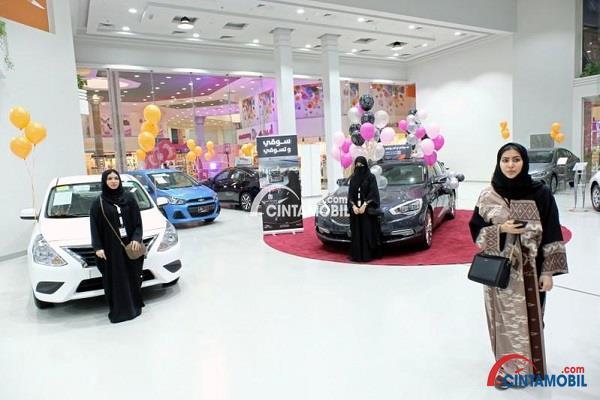 Wanita yang sedang berjalan di dalam pameran mobil dengan beberapa mobil terpampang