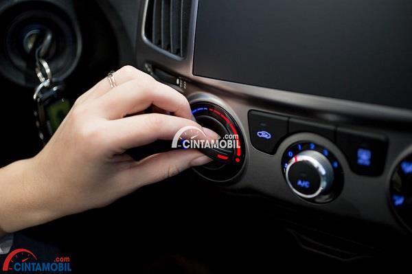 Gambar yang menunjukan tangan yang sedang menyalakan pemanas pada dashboard mobil