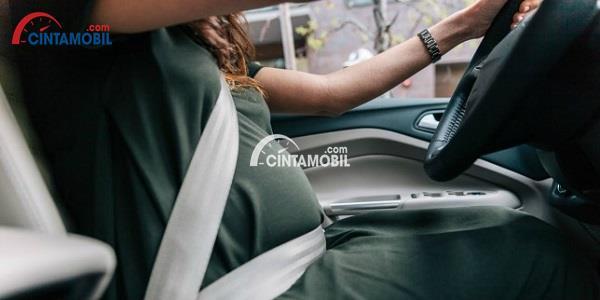Wanita berbaju hijau yang sedang mengemudi di balik setir mobil