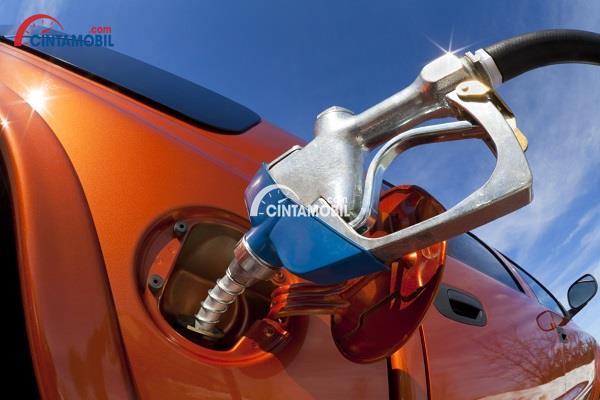 Gambar yang memperlihatkan mobil berwarna orange sedang mengisi bahan bakar