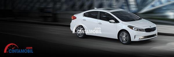 Mobil Kia Forte berwarna putih dengan desain yang simpel sedang melaju di jalanan
