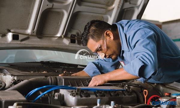 seorang montir yang sedang memperbaiki bagian mesin pada mobil berwarna biru