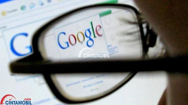 seorang pria berkacamata yang sedang melihat komputer dengan halaman awal google berada pada layar monitor
