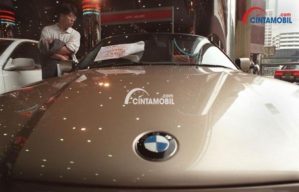 Mobil berwarna perak yang sedang dijual dalam sebuah dealer dan memliki kertas pada bagian jendela depan