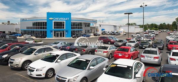 Gambar yang memperlihatkan puluhan mobil yang sedang terparkir pada sebuah parkiran yang besar