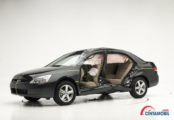 Mobil berwarna hitam yang sedang mengalami kerusakan dengan latar belakang berwarna putih